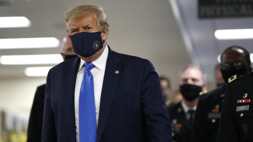 Donald Trump portant un masque bleu marine avec le blason doré de la présidence américaine gravé sur le côté gauche.