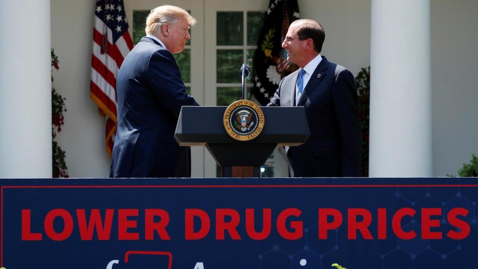 Le président américain Donald Trump serre la main de son secrétaire d'État à la Santé, Alex Azar.