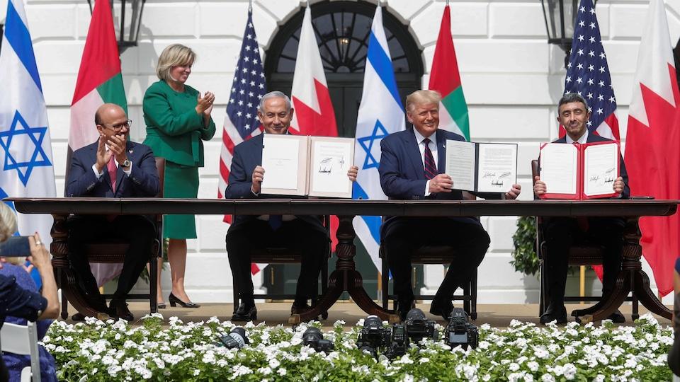 Les signataires présentent des exemplaires de l'accord.