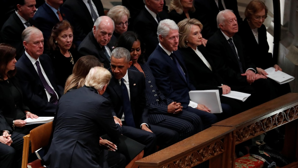 Donald Trump et Barack Obama, assis dans la cathédrale, se serrent la main.