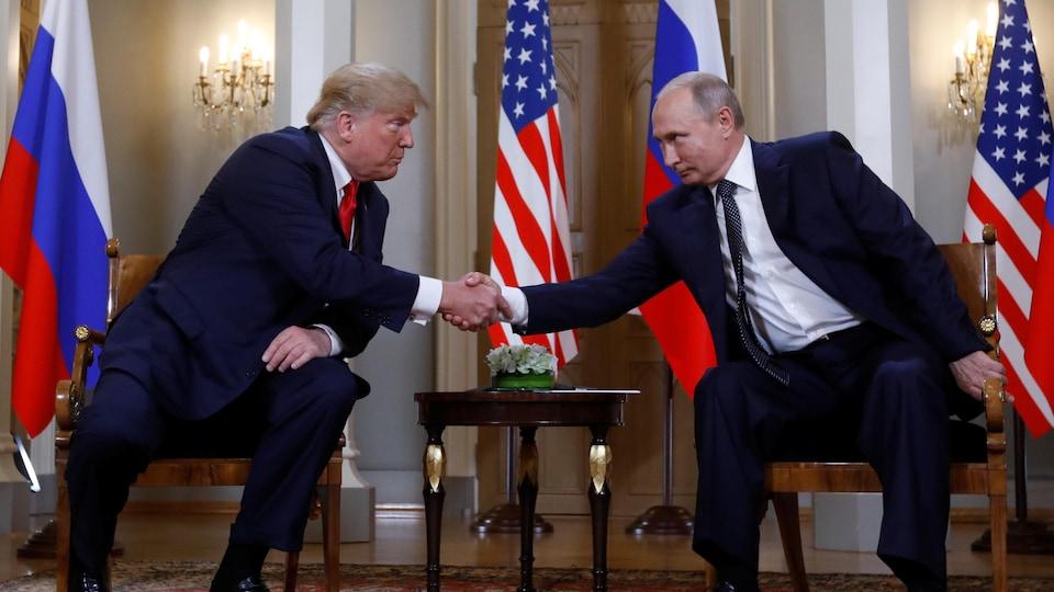 MM. Trump et Poutine se penchent l'un vers l'autre pour se serrer la main.