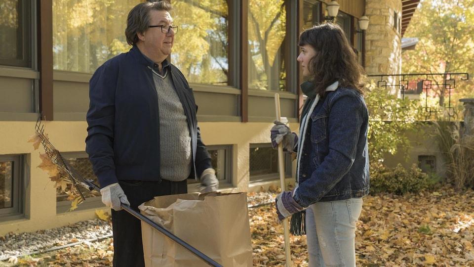 Les deux comédiens sont dehors, en train de racler des feuilles, à l'automne. À gauche sur la photo, Rémy Girard tient un rateau de la main droite et un sac brun, de la gauche. Il regarde Karelle Tremblay, qui tient aussi un rateau dans ses mains, devant lui.