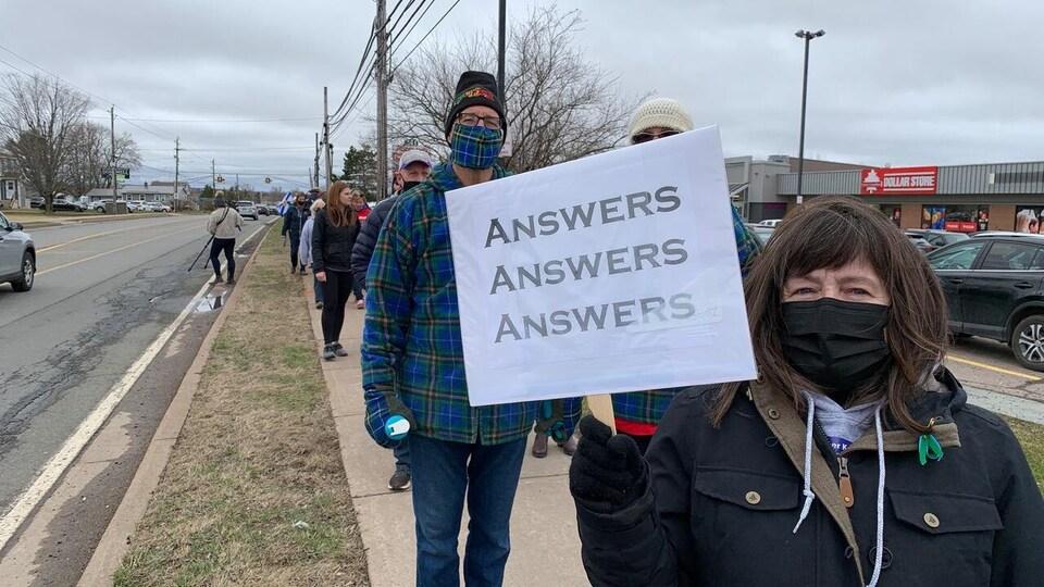 Une femme en bordure de la route montre son affiche sur laquelle est écrit « Réponses, réponses, réponses ».