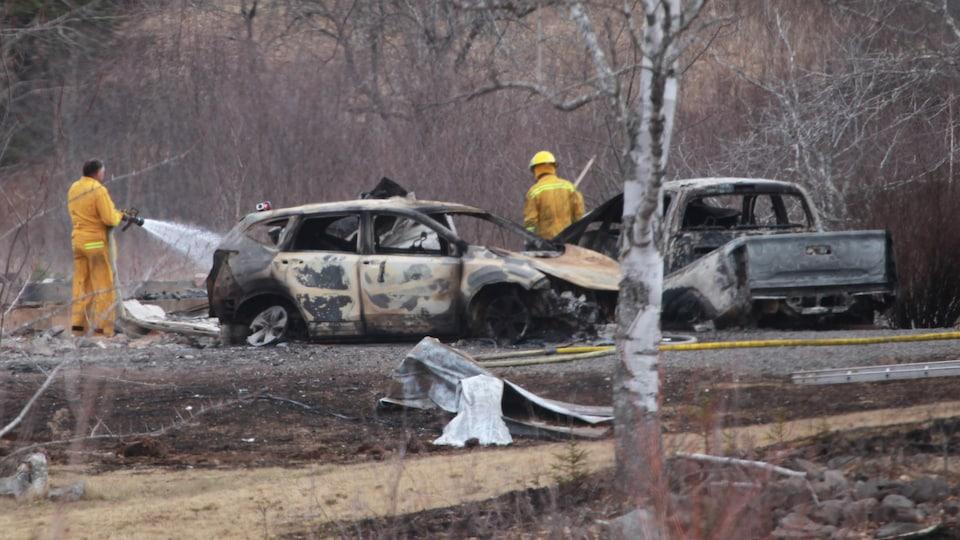 Des hommes habillés en jaune arrosent avec des boyaux des voitures incendiées.