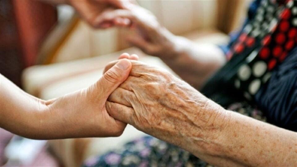 Gros plan sur les mains d'une préposée aux bénéficiaires qui tiennent celles d'une personne âgée.