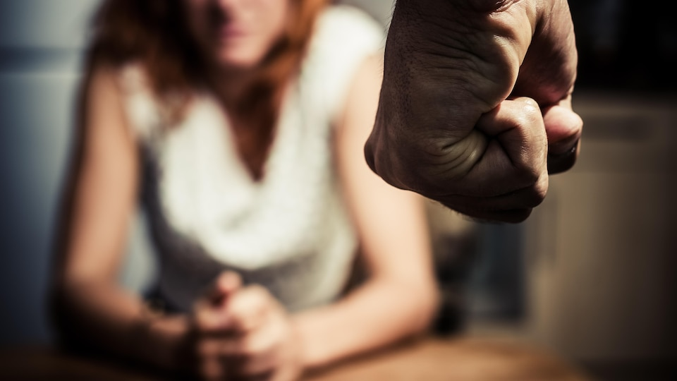 Le poing d'un homme avec la silhouette floue d'une femme derrière.