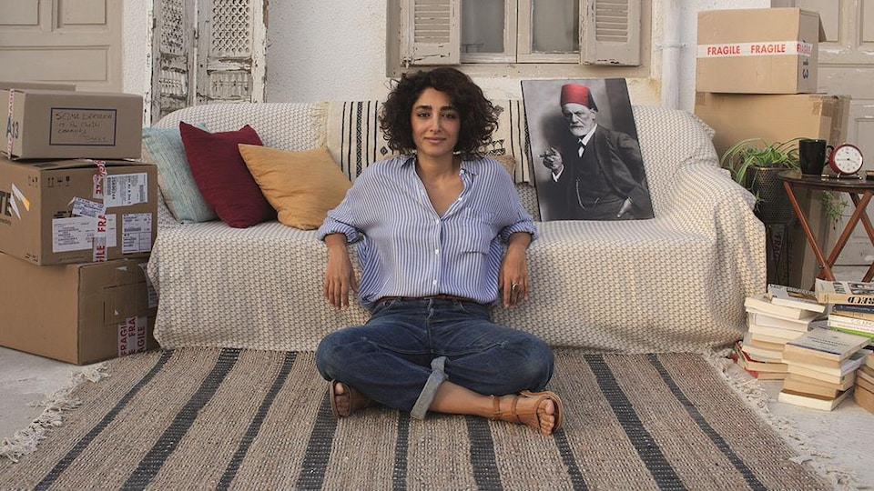 Une femme est assise devant un divan et regarde devant elle.