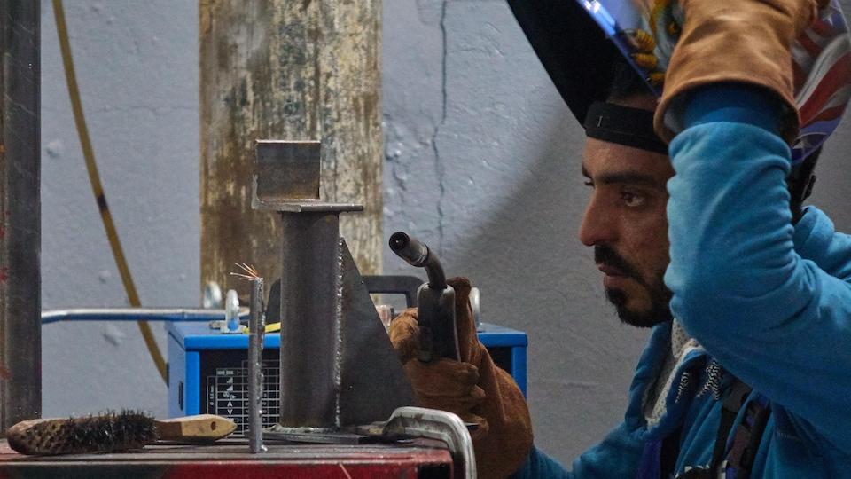 Un soudeur devant sa table de travail.