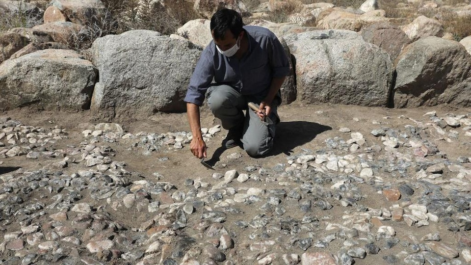 Un homme se penche sur une mosaïque découverte sur un site archéologique.