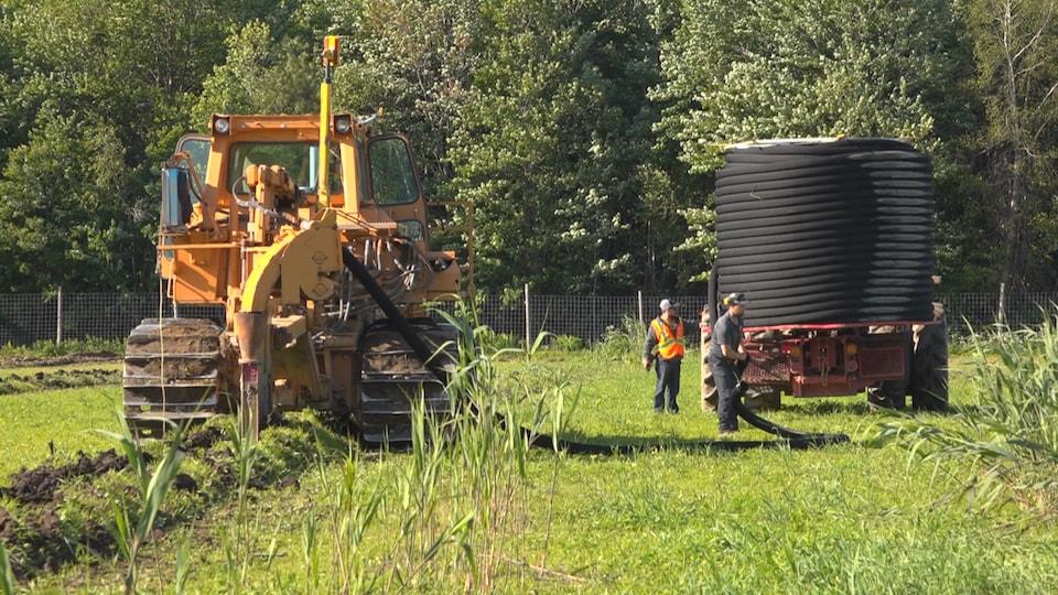 On voit un tracteur sur lequel est chargé un long tuyau de drain enroulé. Des hommes procèdent à son installation.