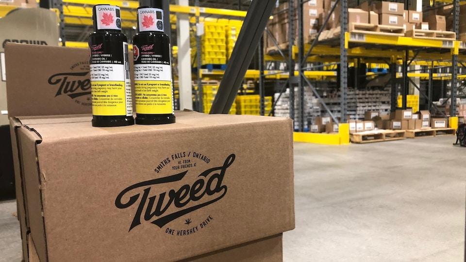 Deux vaporisateurs oraux déposées sur des boîtes de cartons portant le logo de Tweed.