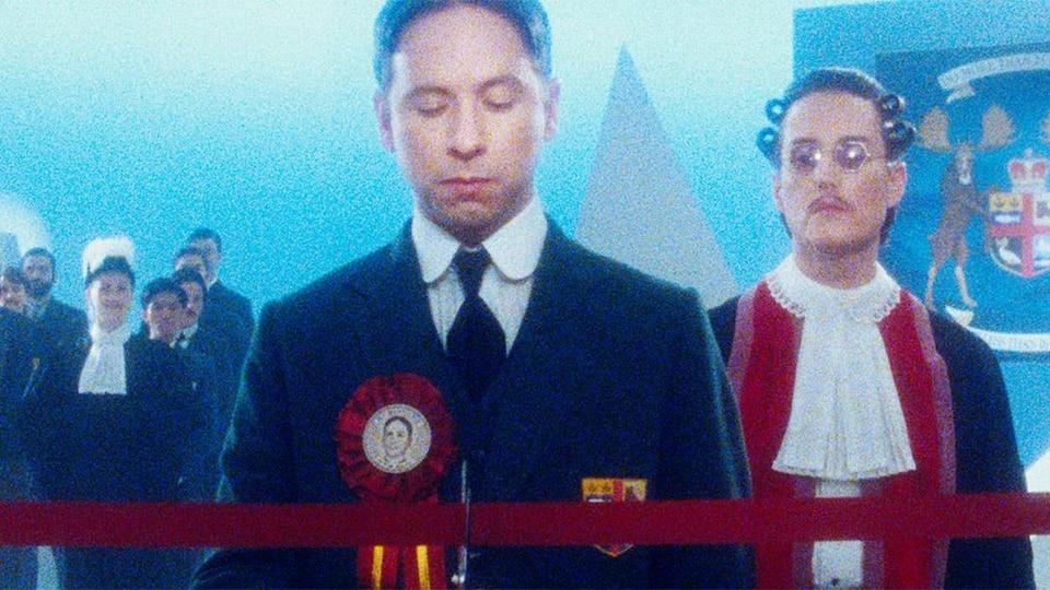Un homme est devant un ruban rouge. Il y  a un juge derrière lui.