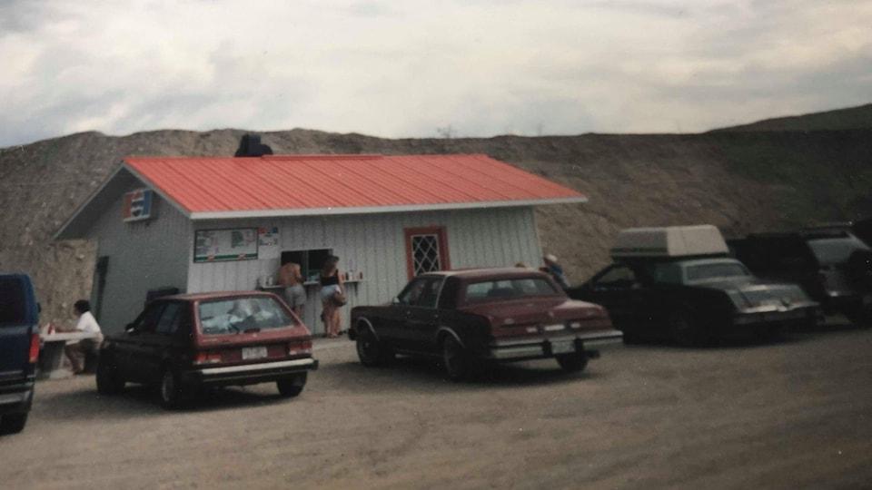Une photo datant des années 80 avec des vieilles voitures et casse-croûte au toit rouge avec une montagne de sable en arrière plan.