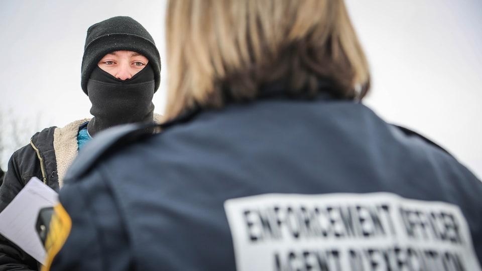 Un manifestant cagoulé fait face à une agente.