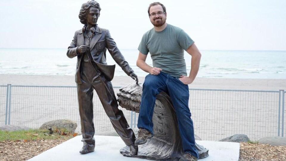 Un homme à côté d'une sculpture de bronze.