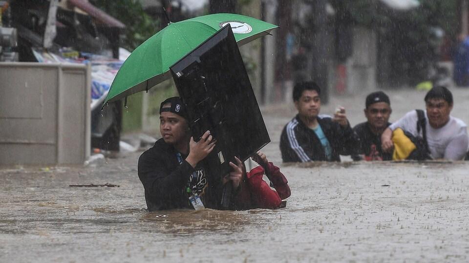 Un homme transporte une télévision dans l'eau qui lui monte plus haut que la taille.
