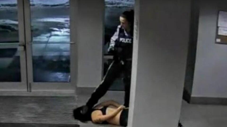 Arrêt sur image d'une vidéo montrant une agente de la GRC appuyer son pied contre la tête d'une jeune femme allongée au sol.