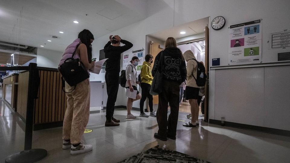 Des étudiants font la file pour voter lors de l'élection fédérale. Une horloge indique qu'il est plus de 21 heures.