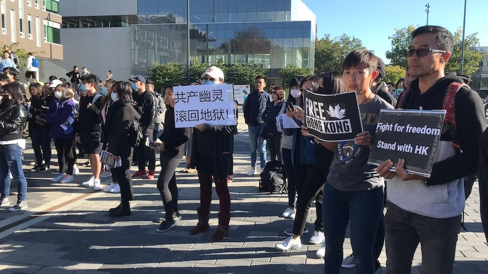 Des étudiants pro-Hong Kong, rassemblés sur le campus de l'université de la Colombie-Britannique, brandissent leurs pancartes.