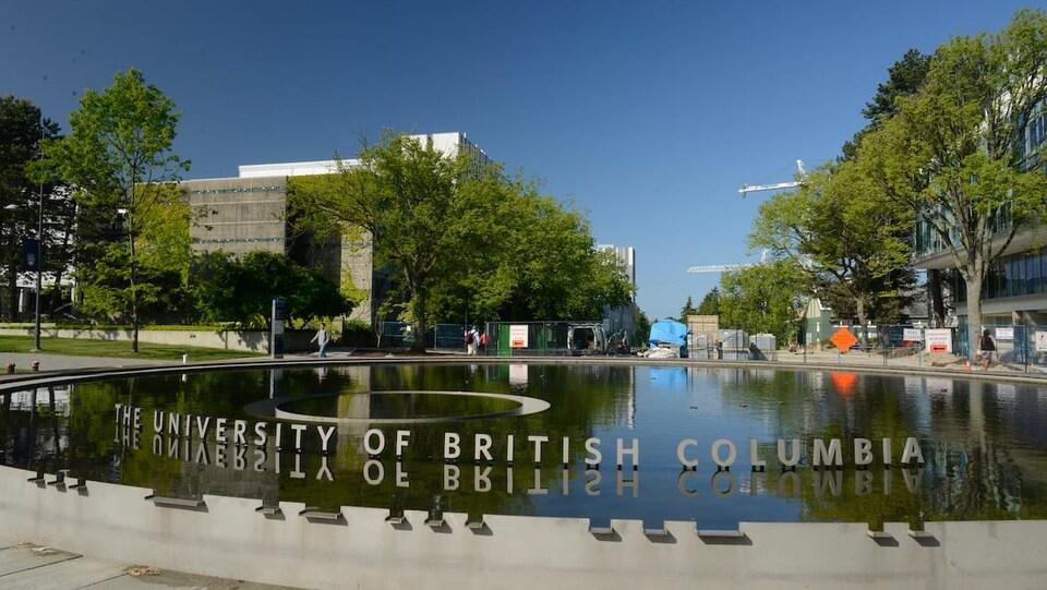 Des lettres (University of British Columbia) se reflètent dans l'eau d'une fontaine, avec des arbres et des bâtiments en arrière-plan.
