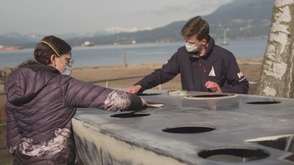 Une jeune femme et un jeune homme polissent la coque d'un petit voilier.