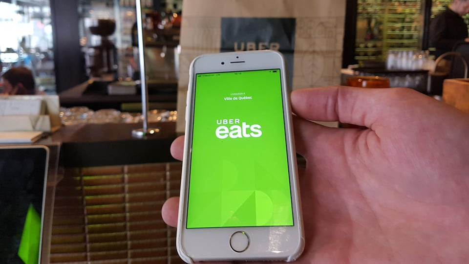 Une main tenant une téléphone cellulaire qui affiche l'application Uber eats
