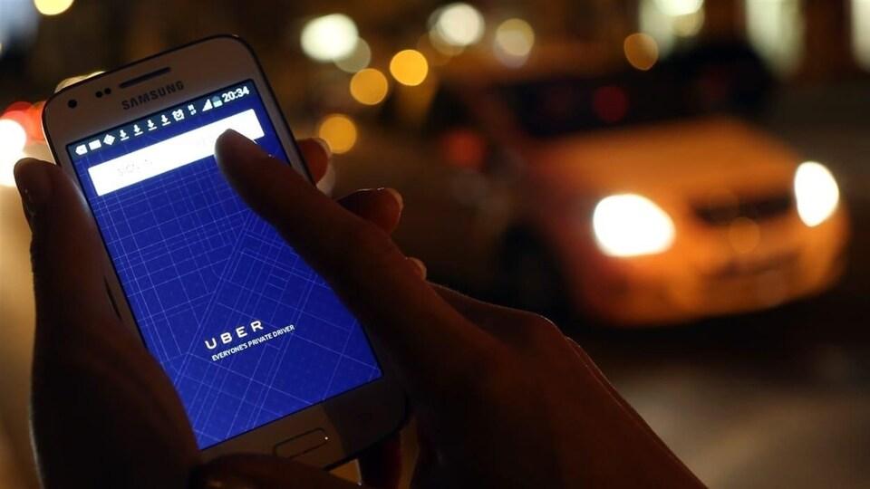 Une main tient un cellulaire dans une rue la nuit.