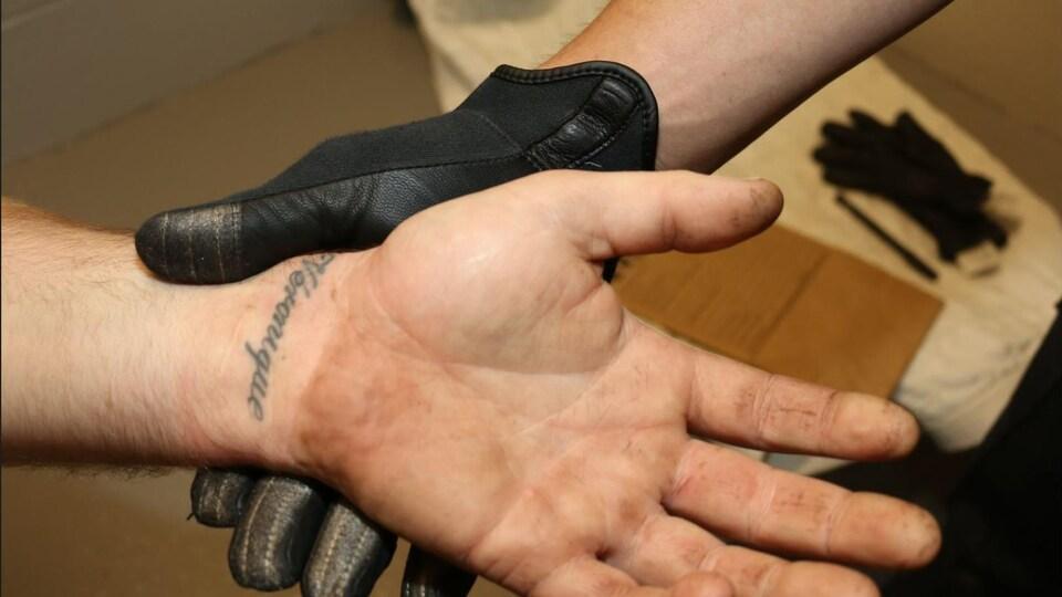Une main gantée tient le poignet d'Ugo Fredette sur lequel on voit le tatouage.