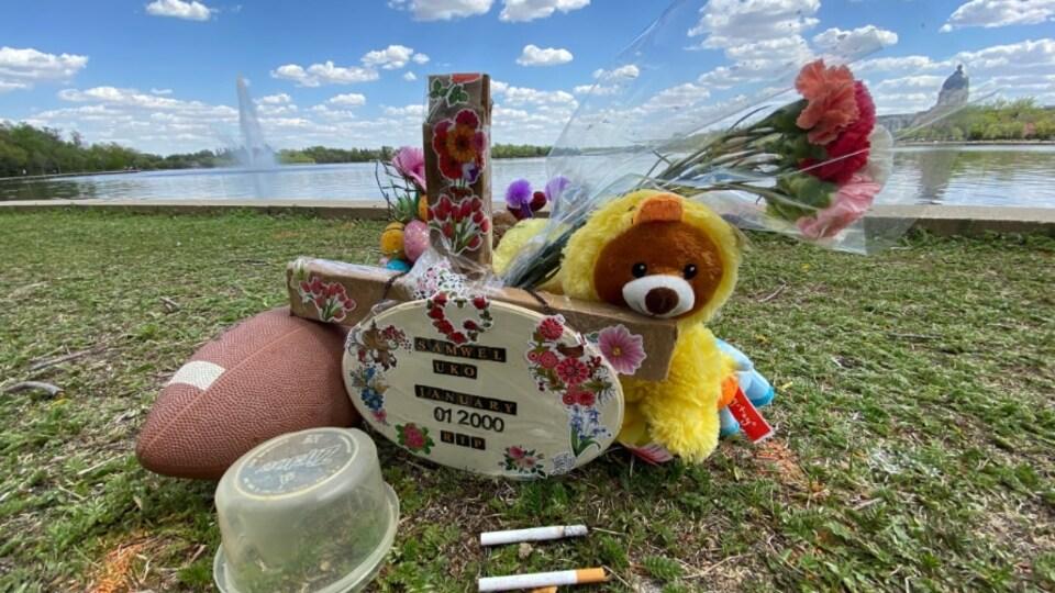 Un mémorial improvisé avec un ballon de football, une peluche, des fleurs, avec le lac Wascana en fond.