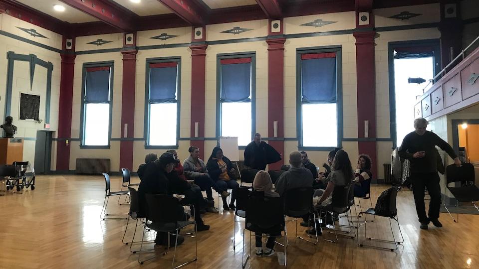 Un groupe d'une vingtaine de personnes est assis en cercle dans une salle de concert.