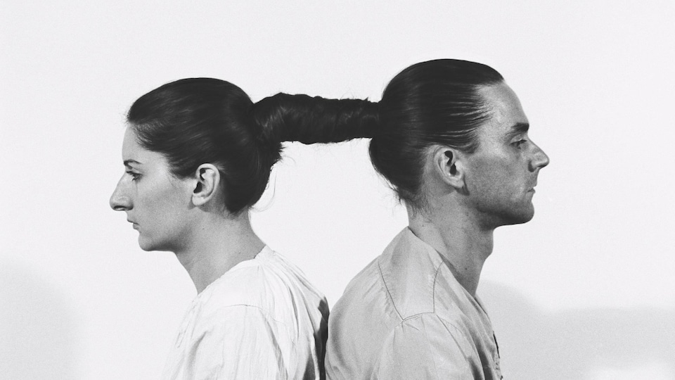 Une photographie qui montre Ulay et Marina Abramovic, dos à dos, les cheveux attachés l'un à l'autre.