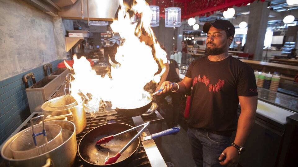 Un cuisinier maniant une poêle en feu.