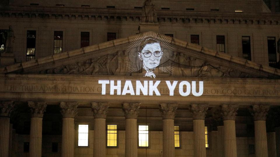 Une image de la juge Ruth Bader Ginsburg projetée sur la façade de la Cour suprême de l'État de New York à Manhattan, avec la mention « Thank you ».