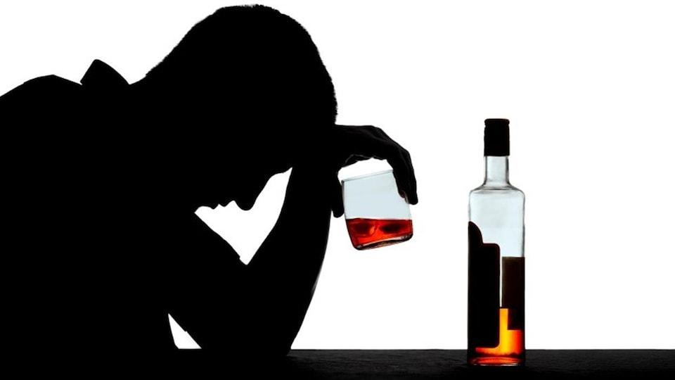 Un homme prend un verre d'alcool.