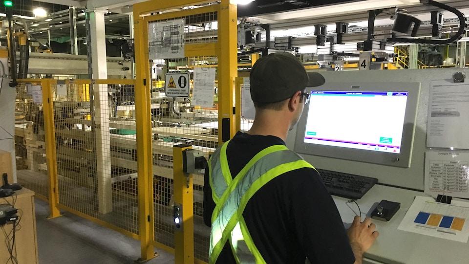 Travailleur devant presse à panneaux