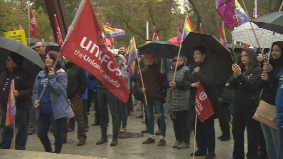 Des travailleurs se tiennent debout dans un parc. ils sont munis de parapluies et de drapeaux avec l'inscription « UniFor ».