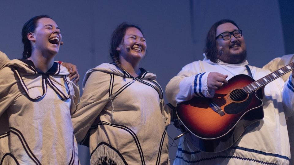 Riant et se tenant par la taille, les deux chanteuses se tiennent debout côte à côte. Un guitariste les accompagne. Tous portent un haut blanc à capuchon, avec des lignes noires au col, à la taille et aux poignets.