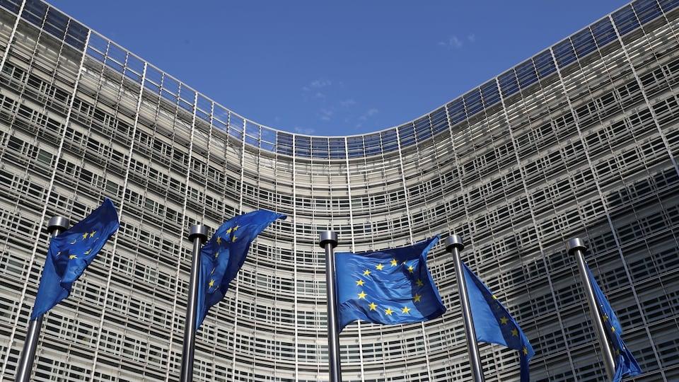 Cinq drapeaux de l'UE flottent devant un bâtiment concave à Bruxelles.