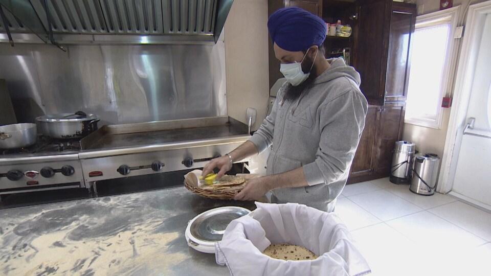 Un homme, qui porte un turban, un masque et des gants, prépare des galettes dans une cuisine communautaire.