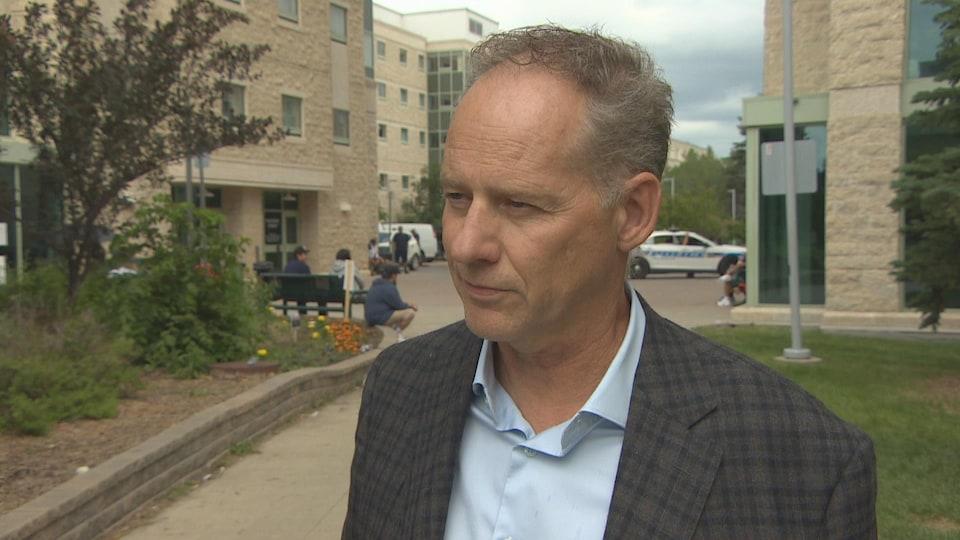 Paul Dederick, debout, donne une entrevue en plein air sur le campus de l'Université de Regina.