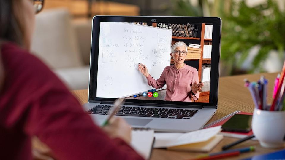 Un ordinateur portable ouvert. On voit à l'écran une professeure d'université donnant un cours.