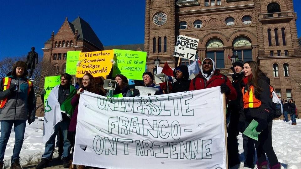Des étudiants manifestent en hiver avec des banderolles.