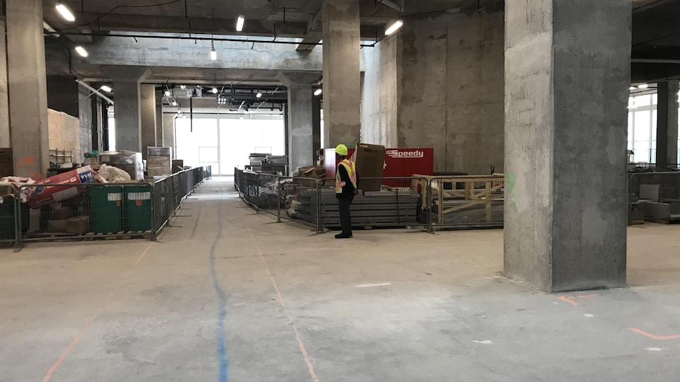 Un espace bétonné avec du matériel de construction et un travailleur avec un casque de sécurité.