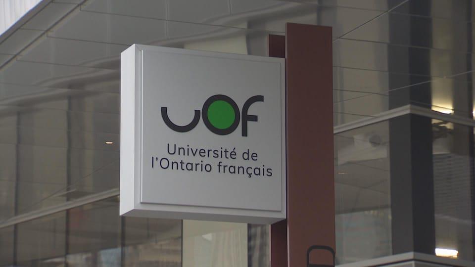 Affiche près d'un immeuble sur lequel on peut lire UOF, université de l'Ontario français.