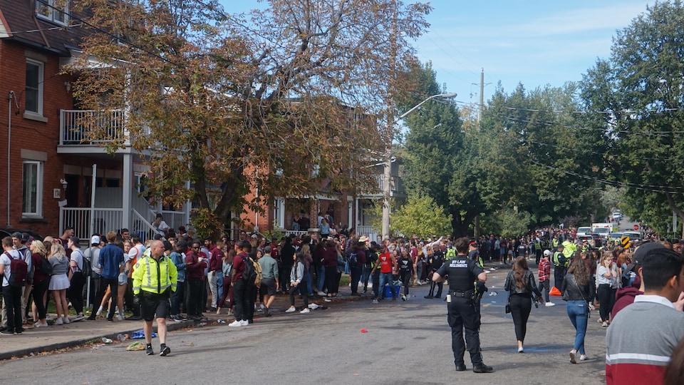 Des policiers dans la rue surveillent des jeunes fêtards de par et d'autre de la rue.