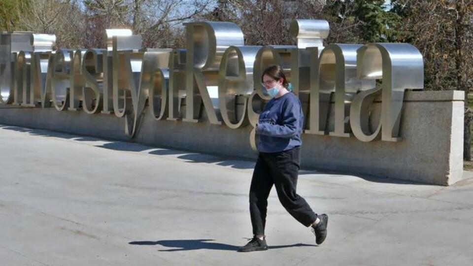 Une étudiante marche devant les lettres géantes en métal sur le campus, qui indiquent le nom de l'Université de Regina.