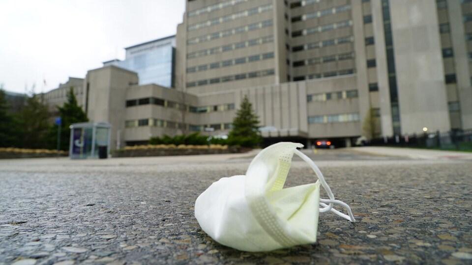 Un masque jeté sur la chaussée devant un hôpital.