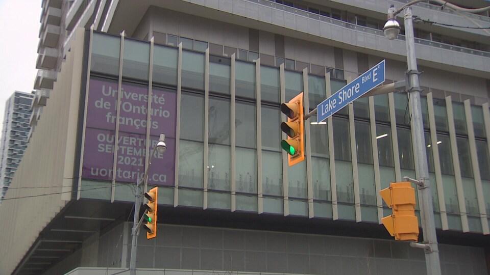 Une affiche dans la fenêtre d'un immeuble à une intersection annonce l'ouverture de l'Université.
