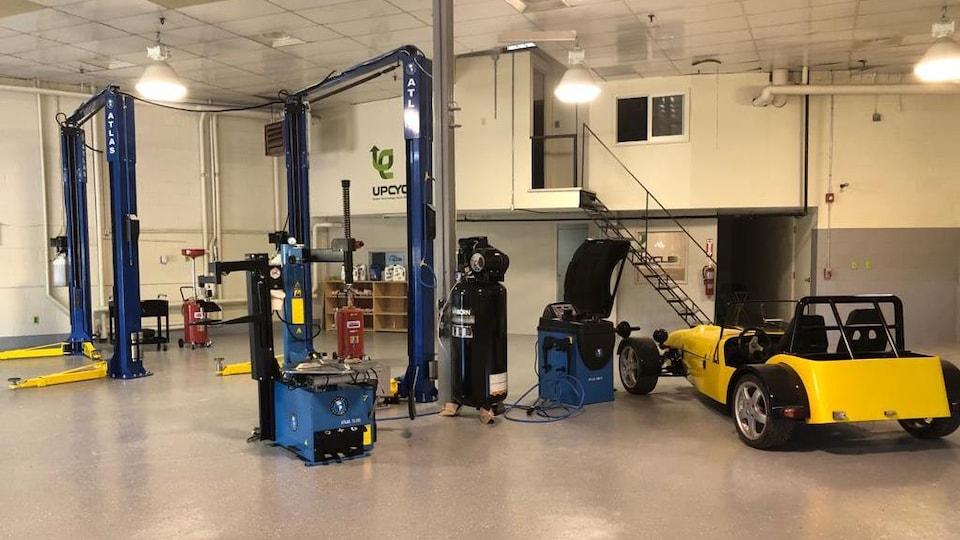 L'intérieur de l'entreprise Up Cycle Green Tech, avec des équipements de réparation de voitures et une voiture électrique garée.
