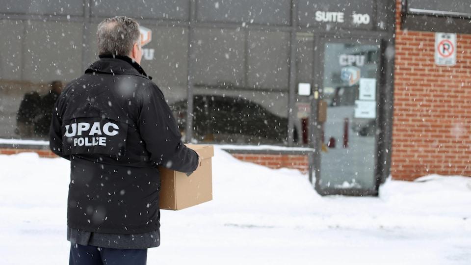 Un enquêteur de l'UPAC tient une boîte dans ses mains à proximité des bureaux d'une entreprise.